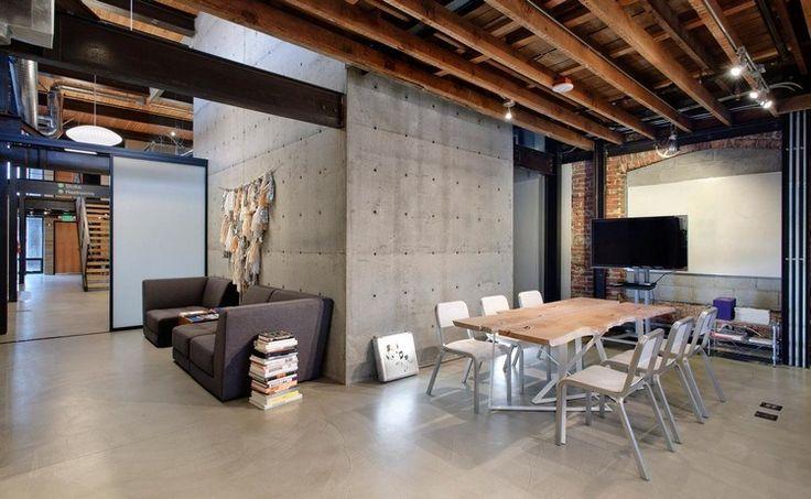 déco industrielle, murs en béton banché, table ne bois brut et chaises métalliques assorties