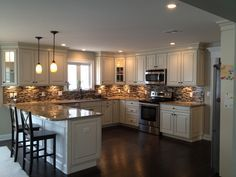 U shaped kitchen with peninsula design with American Woodmark cabinets; Savannah Maple white with hazelnut glaze... Mosaic glass and stone tile. Stainless steel appliances... My dream kitchen come alive.