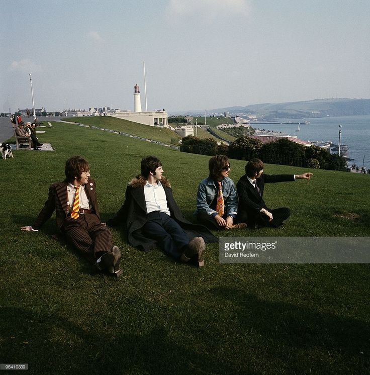 John Lennon, Paul McCartney, George Harrison and Ringo Starr of The Beatles pose for a group shot, sitting on the grass at Plymouth Hoe looking out to sea on September 12th 1967 during the filming of 'Magical Mystery Tour'. Image is part of David Redfern Premium Collection.