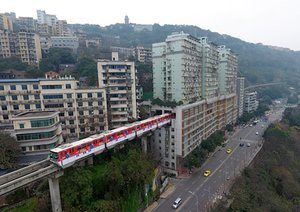 light-rail train passes through a 19-storey residential building that also serves as a station in the Chongqing Rail Transit system in  China
