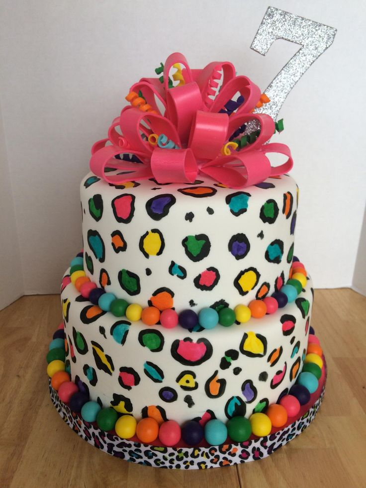 "Rainbow Leopard Cake - This is my daughter's 7th birthday cake. 8"" & 10"" rounds. Strawberry cake with banana-chocolate filling. Covered with fondant and hand-painted. Fondant-loop bow with fondant curlicues and fondant ball border."
