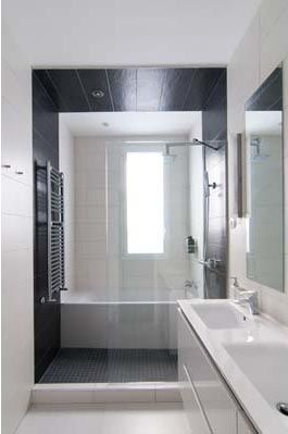 una caja de pizarra gris en la ducha enmarca la baera y destaca en el blanco
