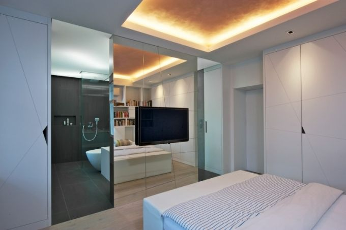 Ložnice má spoustu úložných a odkládacích prostor - skříně, zásuvky pod postelí, policový systém integrovaný do hlavní stěny i jednoduchý stůl pod oknem. K útulné atmosféře přispívá po obvodu místnosti snížený strop se zabudovaným nepřímým osvětlením i masivní podlaha z běleného dubu