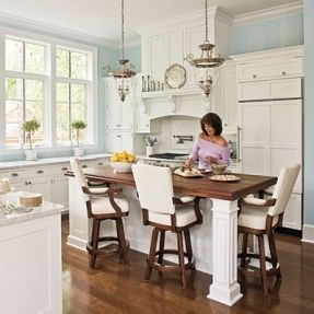 Elegant White Kitchen - modern appliances peacefully coexist with graceful glass lanterns and cushy swivel-seat barstools, vertical stripes painted in two subtle shades of blue create a soothing atmosphere, many of the kitchen's features have the feel of