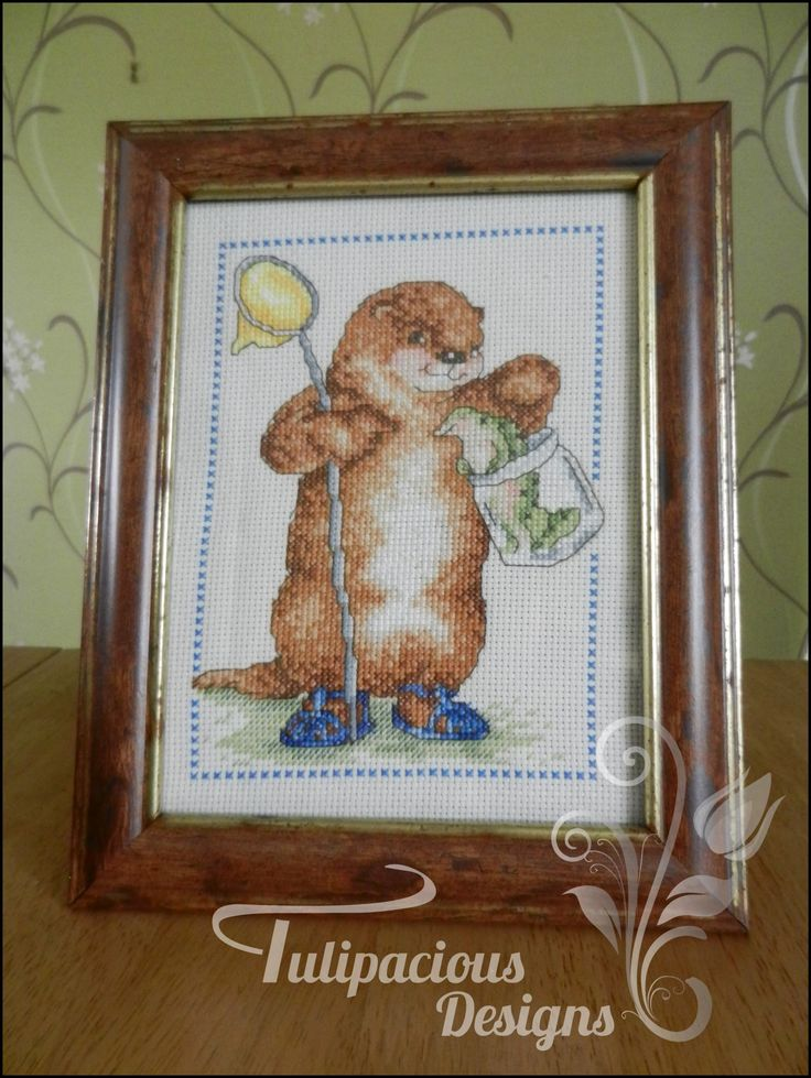 an otter fishing, cross stitched and framed by tulipacious designs.