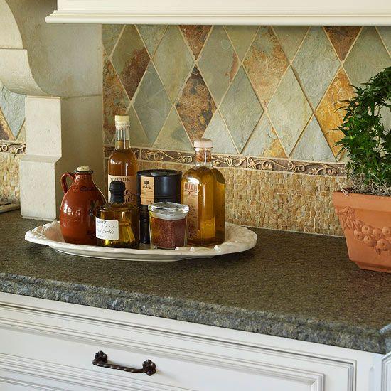 Mosaicos calcáreos forman la base de la pared posterior de esta inspiración europea cocina . La barra de revestimiento de bronce por encima de ellos complementa la campana extractora de cobre mientras azulejo de la pizarra en un romántico arlequín patrón añade sutiles de color .