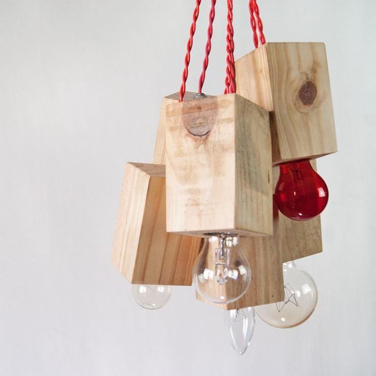 Essa luminária pendente é feita com pedaços de pontalete e fios coloridos. A combinação de materiais simples e industriais em uma estrutura aglomerada, ao ser suspensa, consegue um resultado delicado.