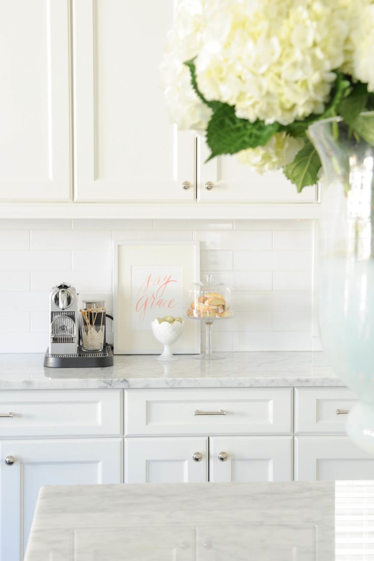 white cabinets, marble countertop, white subway tile backsplash, silver traditional hardware