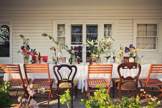 A variety of flower arrangements paired with mismatched chairs adds a whimsical element to this rustic wedding reception.