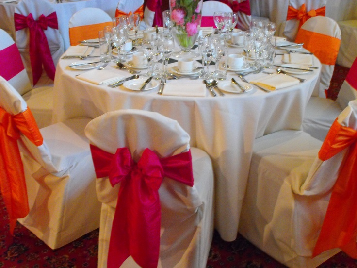 Alternating Fuschia Pink and Orange Satin Bows on White Chair Covers