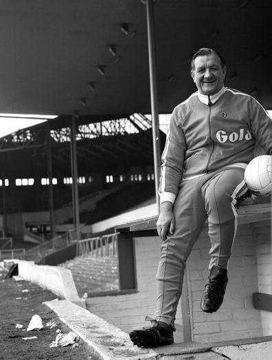 1974. Liverpool FC Manager Bob Paisley is pictured sitting next to the home dugout at Anfield.