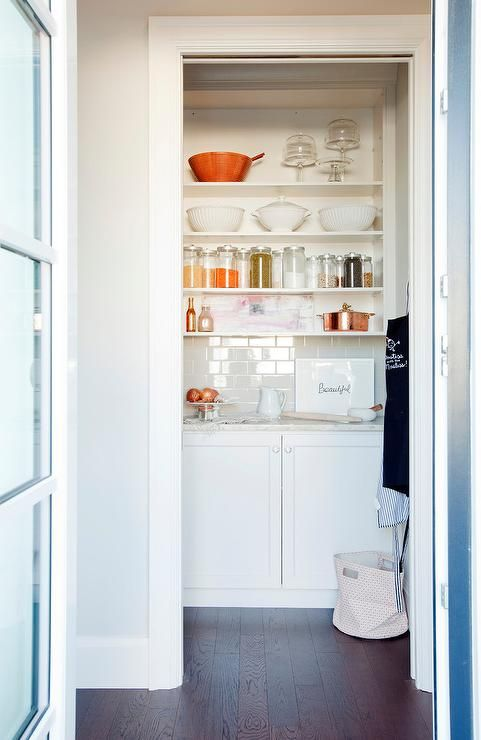 kitchen pantry features white base cabinets topped with white marble countertops and a pale gray subway tile backsplash under stacked floating shelves