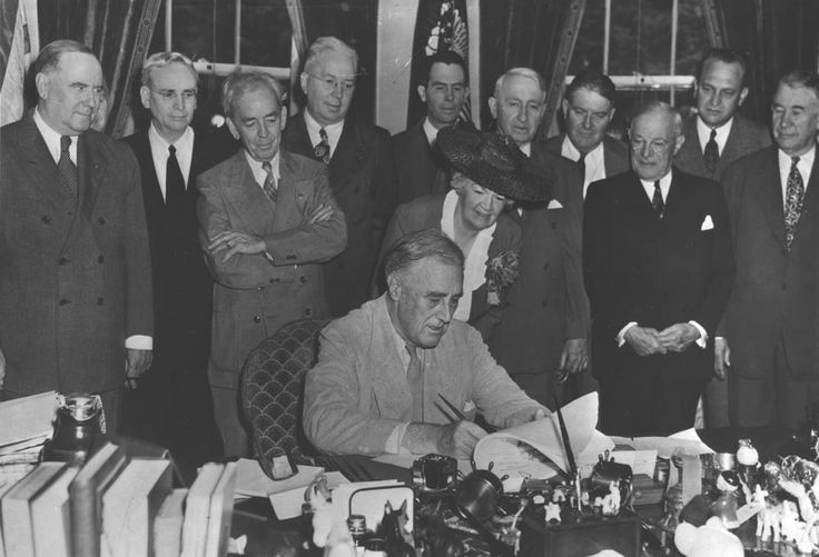 """FDR signs the G.I. Bill in the Oval Office, with (l to r) Bennett """"Champ"""" Clark, J. Hardin Peterson, John Rankin, Paul Cunningham, Edith N. Rogers, J.M. Sullivan, Walter George, John Stelle, Robert Wagner, (unknown), and Alben Barkley; June 22, 1944. FDR Library Photo Collection, NPx 64-269."""