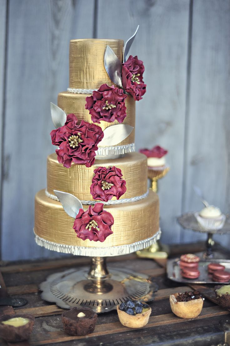 A gorgeous gilded cake with rustic floral accents is perfect for a glam bohemian wedding.