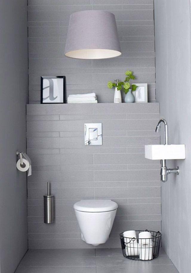 Baño estilo minimalista en tonos grises incluyendo piso, cielo y muros. Sobre el inodoro una lámpara colgante de pantalla de tela en color gris. El muro del inodora crea una repisa donde vemos un cuadro pequeño de marco negro, un par de toallas blancas y un florero celeste con flores amarillas.
