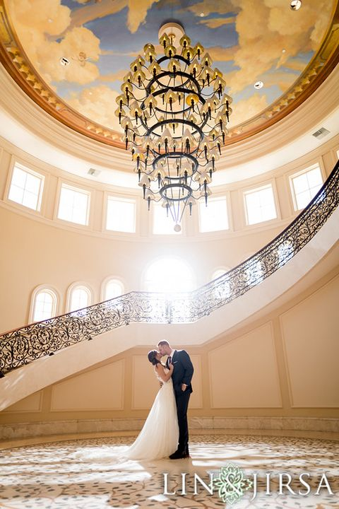 Orange county outdoor wedding shoot bride tulle ball gown with lace detail bodice and thin spaghetti straps with open back design and groom slate blue suit with matching vest and white dress shirt with long burgundy tie and white pocket square kissing under hanging chandelier