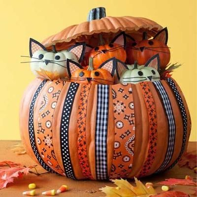 No-carve Halloween pumpkin crafts: Kitty Pumpkin craft with many small cat pumpkins inside a larger one, covered with festive ribbon