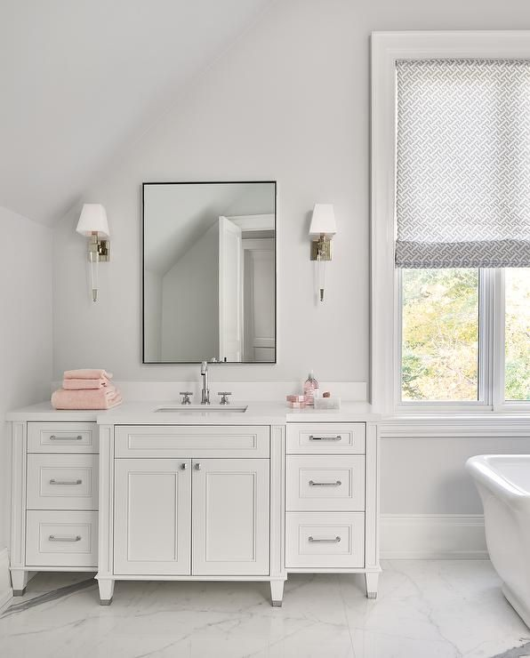 Glass And Nickel Sconces Mounted To A Light Gray Wall Flank A Thin Black Frame Mirror Hung Above A White Bathroom Designs Black Mirror Frame White Mirror Frame