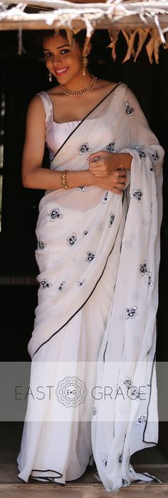 Presenting the royal Iris on a milky white, ethereal pure chiffon saree with pallu adorned with white and black Iris flowers, exquisitely handcrafted with silk shading. Here's a six yards of your statement black-and-white color palette, fresh and welcoming, off the beaten path.