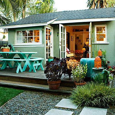 Love EVERYTHING about this one. The idea to paint the white benches a bright turquoise, choosing colored plants for color, and spray painting lanterns. Color oh my!