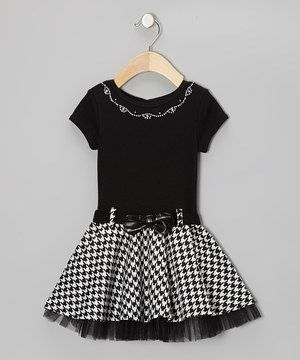 Trimmed in tulle and impressive in houndstooth, this scholarly style has learned a thing or two about fun fashion—frill goes a long way. A button at the back and snap closure belt help it fit as nicely as an easy A.