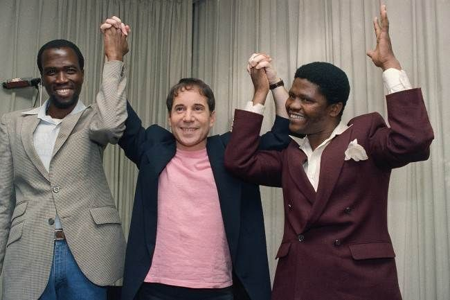 """Singer-songwriter Paul Simon is joined by Albert Mazibuko, left, and Joseph Shabalala, right, at a news conference in New York, Aug. 25, 1986, to introduce Simon's new album, """"Graceland."""" Mazibuko and Shabalala are two of the many South Africa musicians and singers who collaborated with Simon on his new album which blends the sounds of American pop music with that of black South Africa. (AP Photo/Marty Lederhandler)"""