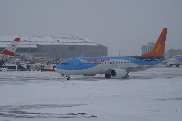 A Colourful Sunwing Airplane in Snowstorm at Toronto Pearson Airport