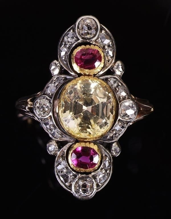 A late Victorian yellow sapphire, ruby and diamond ring, circa 1880, the central cushion shaped mixed cut yellow sapphire rub over set between two oval mixed cut rubies to either side, in a tapering mount set with old cut and rose cut diamonds with palmette ends, mounted in gold backed silver above bifurcated shoulders.