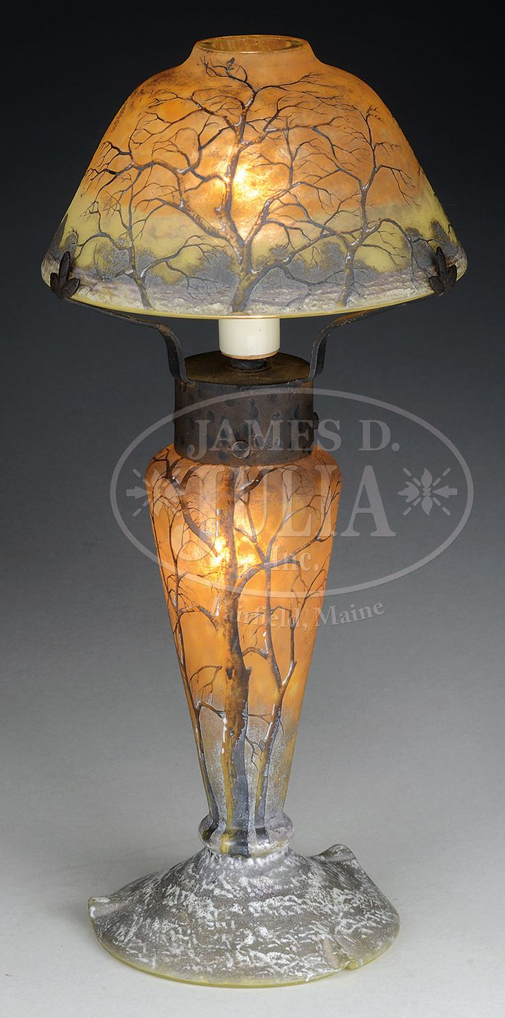 "DAUM WINTER SCENE CAMEO GLASS LAMP. Daum lamp has cameo and enameled decoration of a winter scene with barren trees and snow covered ground against a mottled yellow and orange sky. The foot is enameled in white depicting a snow covered ground while the trees are enameled in shades of brown with patches of white snow adhering to the bark. Lamp is signed on underside in black enamel ""Daum Nancy"" with a cross of Lorraine."