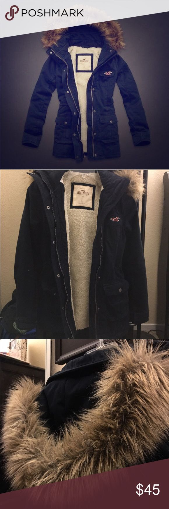 Hollister Twill Navy Blue Parka This is a twill navy parka from Hollister! I tried to model it although it hardly fits me as you can see. There are also adjustable ties on the inside of the jacket to make it cinch more at the waist or open it up. To give you an idea, I am 5'8 and this is how it fits on me. Also the fur on the hood is detachable, and there is a pocket in the coat to place an MP3 player or phone and a port to feed your headphones through Hollister Jackets & Coats
