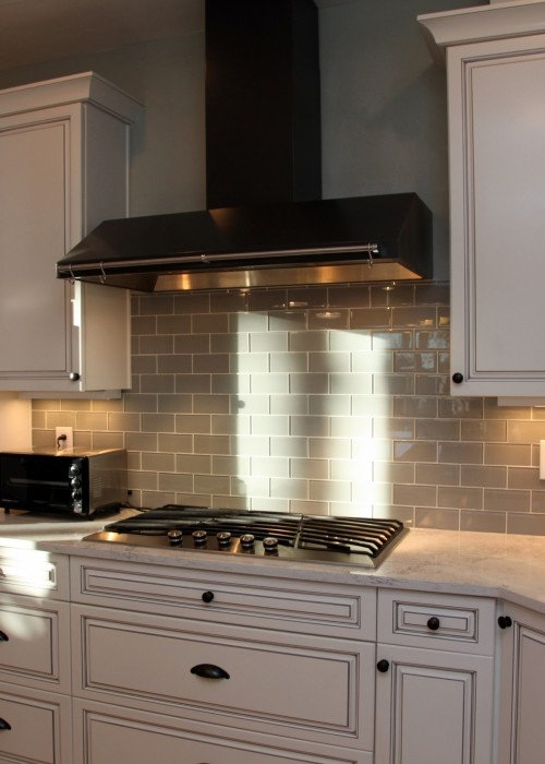 grey subway tile looks great next to the white cabinets and stainless steel appliances