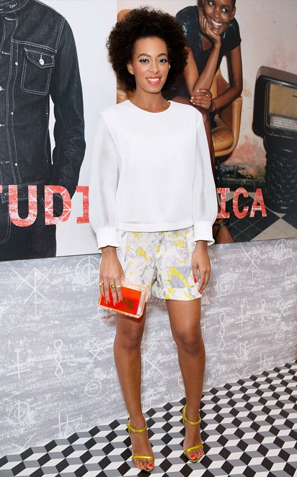 Solange Knowles wears a white blouse, printed shorts, yellow sandals, and a red lucite clutch