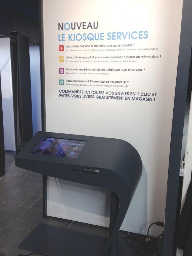 La Borne Service de Kiabi En libre-service, destinée aussi bien aux clients qu'aux conseillères de vente. Stratégiquement placée dans la zone services, qui regroupe les cabines d'essayage, la retouche et le SAV, elle embarque une tablette tactile, un lecteur de code-barres pour scanner les étiquettes des produits et une imprimante thermique pour délivrer les tickets de réservation. Egalement connectée en Wi-Fi au système d'information de Kiabi pour l'accès au catalogue et aux stocks.