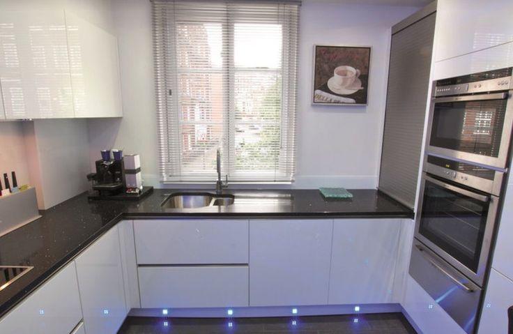 белая П-образная кухня модерн с черной столешницей и LED-подсветкой цоколя