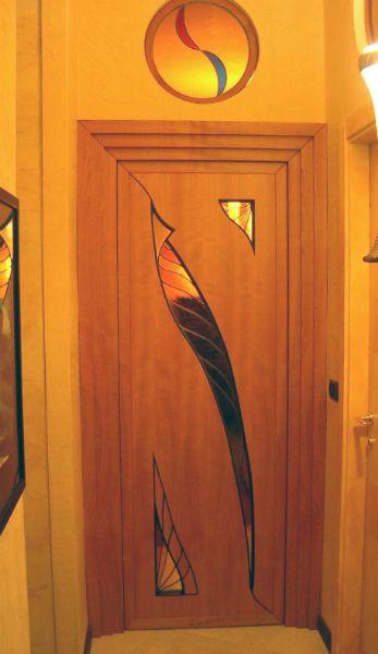 Porta in varie essenze di legni pregiati con inserti in vetro colorato lavorato e rilegato in piombo.