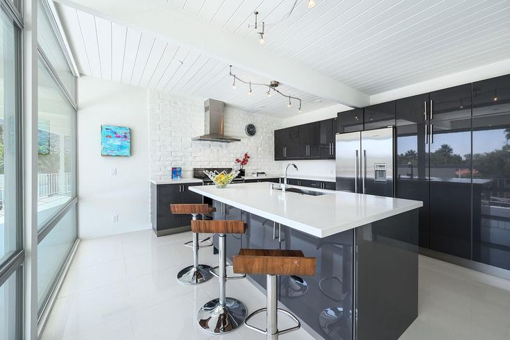 Kitchen features ultra-modern look with glossy grey cupboard surfaces and island, white countertops, stainless appliances and minimalist white tile flooring. Wood seat stools sit at island.