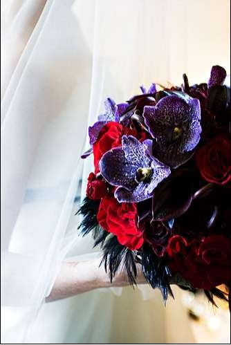 Purple red and black wedding bouquet with black feather accents.