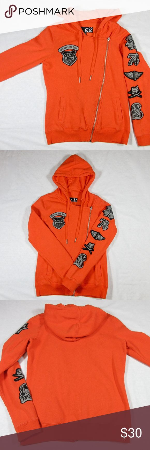 "Fox Racing Hoody, Women's S, M  Body Con, Orange Pre-owned Fox Racing hooded sweatshirt.  Stunning orange with black and gray decals.  Asymmetric zipper closure.  An inner snap holds the fabric in back in place.  Curves in a bit at the waist, making this a very flattering, semi body con hoodie.  Marked a Women's M.  Will also fit a small.  Chest, 36"" -- Sleeves, 23"" -- Length from back neck to lower edge, 23"".  Pre-owned but in very good condition with no flaws to note. Fox Racing Jackets…"