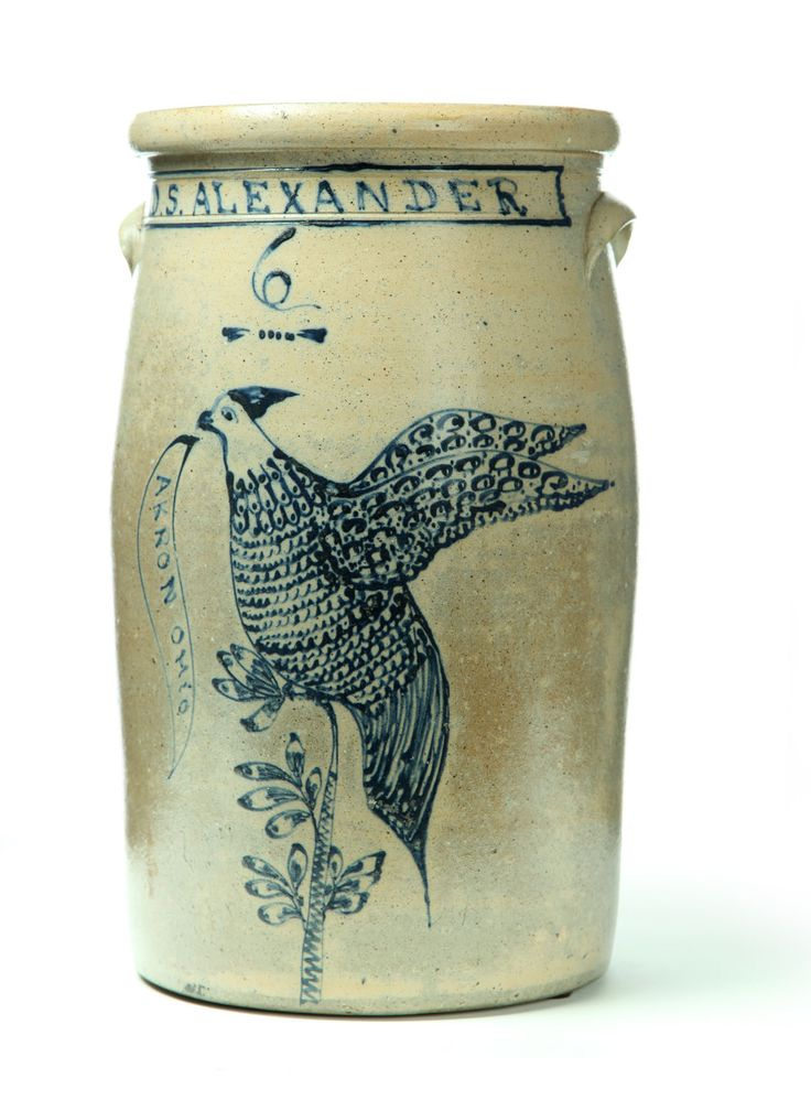"RARE OHIO STONEWARE CHURN.  Summit County, Ohio, 1865-1880. Six-gallon of typical form, decorated in cobalt with an elaborate bird on a branch, holding in its beak a banner reading ""Akron, Ohio' and under the name ""D.S. Alexander.' Imperfections"