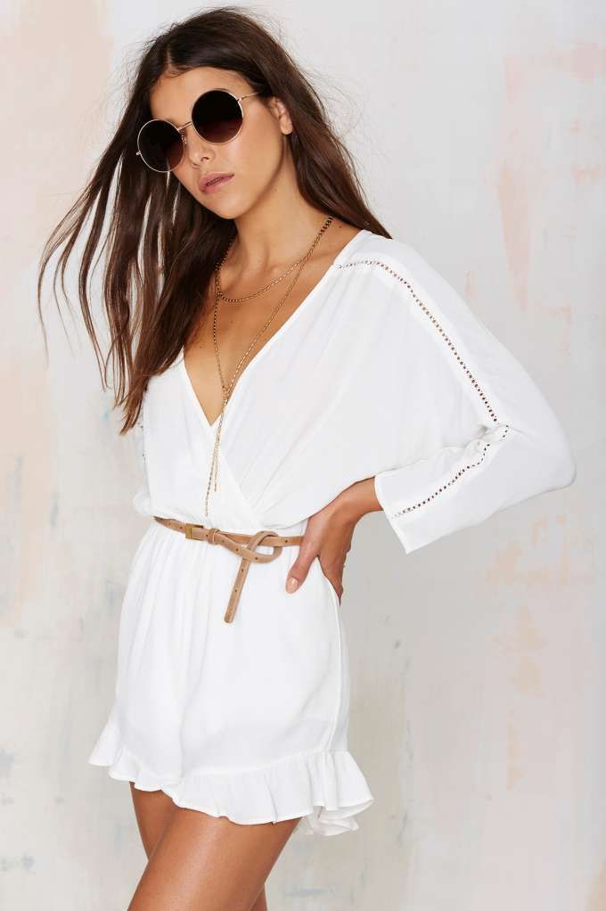 Good vibes only in the Feelin' Myself Crossover Romper in a light white crepe with crochet details and a ruffle hem.