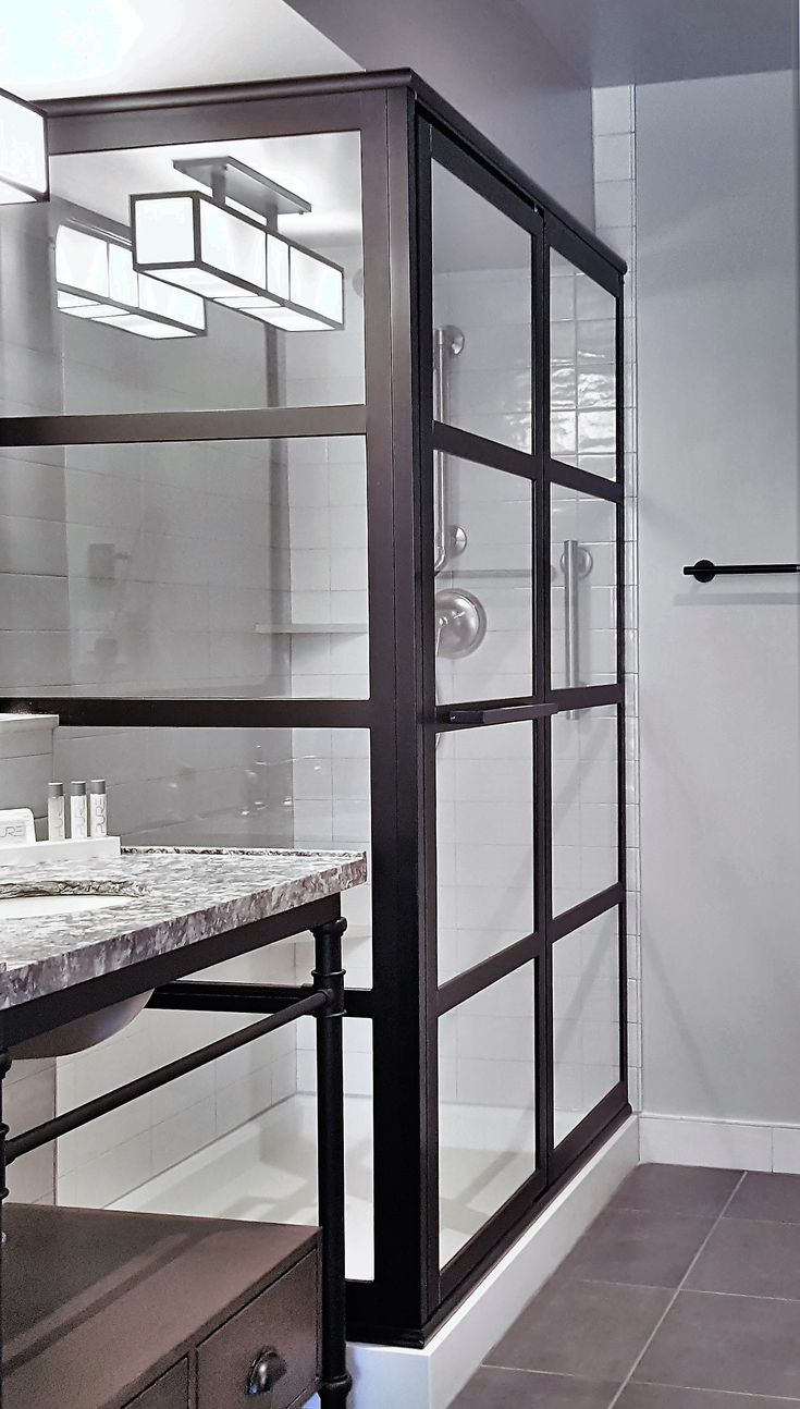 """Gridscape Series GS2 Corner Swinging Shower Door by Coastal Shower Doors.    Black-bronze anodized finish with clear tempered glass.     For more """"steel"""" framed industrial modern factory windowpane shower doors visit:  www.coastalshowerdoors.com"""