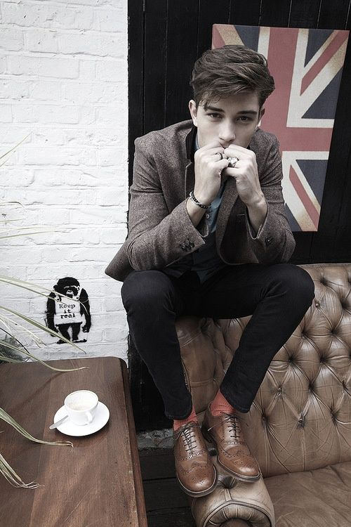 British flag and Chesterfield sofa, to the implied cup of tea and nod to  Banksy, to the model's hair, clothes and brogues.