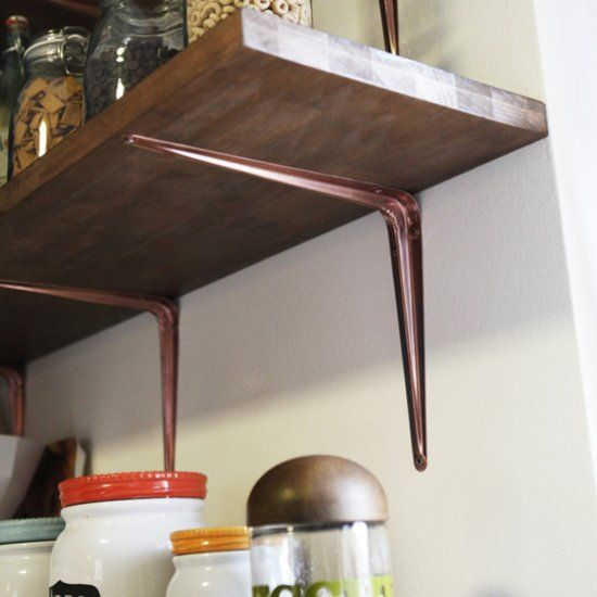 Spruce up cheap shelving brackets with a coat of metallic copper paint to make them pop!