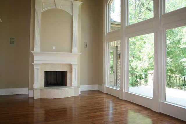 The two-story grand room with beautiful hardwood flooring and floor-to-ceiling wall of windows boast a grand fireplace!
