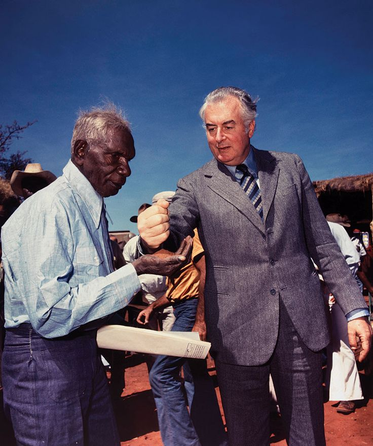 Prime Minister Whitlam pouring dry earth into the palm of Mr Vincent Lingiari. Mr Lingiari holds leasehold title document in other hand.