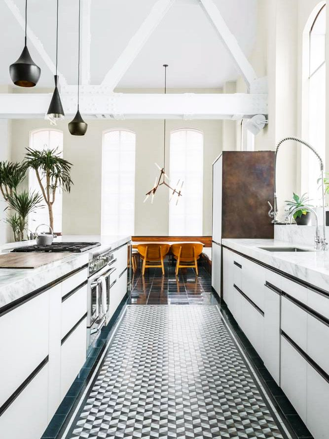 Loft kitchen with tiled floor and modern white cabinetry on Thou Swell @thouswellblog