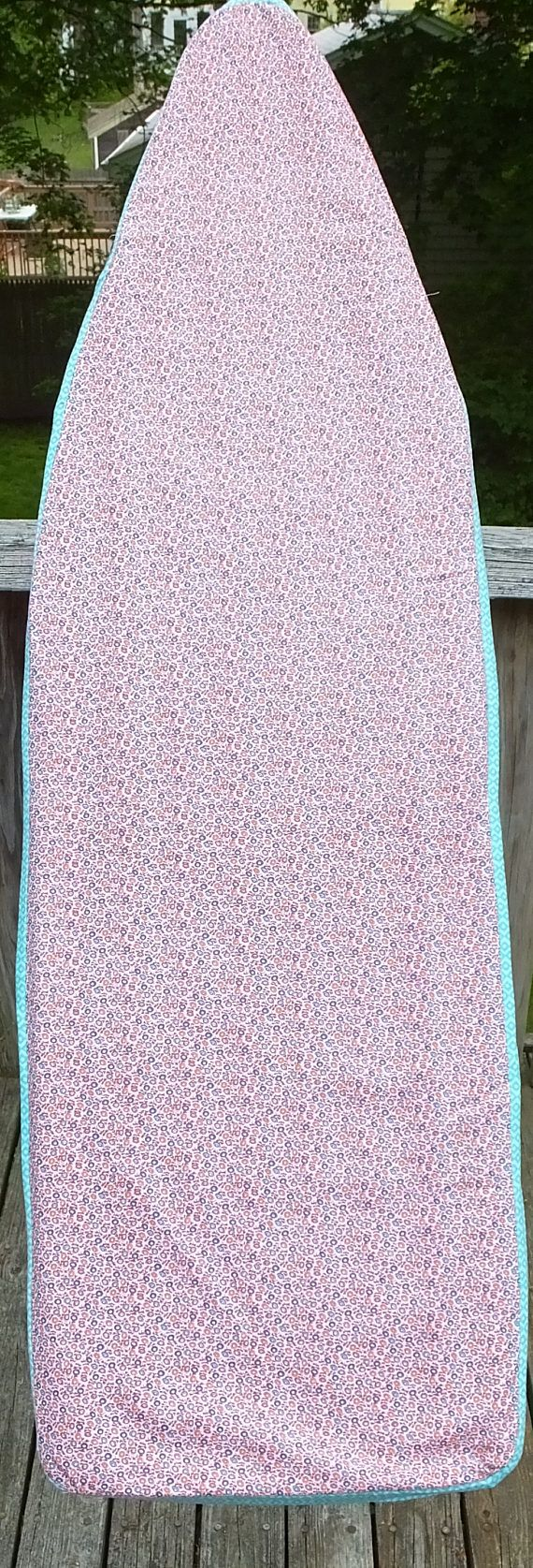Beautiful vintage fabric ironing board cover was created from 100 % cotton vintage floral print fabric for the top and accented with contemporary turquoise fabric along the sides. This cover is very lightweight and lined with Pellon Insul-Fleece for thermal protection and should easily fit over any extra padding if you have it. This cover is designed to fit a standard 54 x 14.5 ironing board. The cover measurements from side to side are 58.75 x 20.5 and has a drawstring all around to pull…