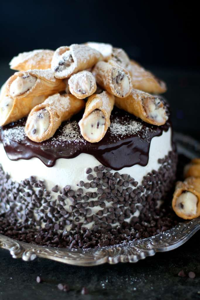 cannoli cake; fluffy and moist buttermilk cinnamon cake; filled with a cinnamon ricotta frosting with cannoli shells and mini chocolate chips; covered in a cinnamon Italian meringue buttercream topped with chocolate ganache