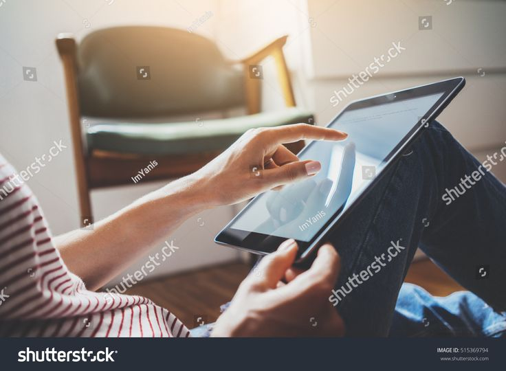Close-up image of young freelancer girl typing on touch screen of digital tablet while sitting at comfortable home interior, female hands using tablet pc device, flare light