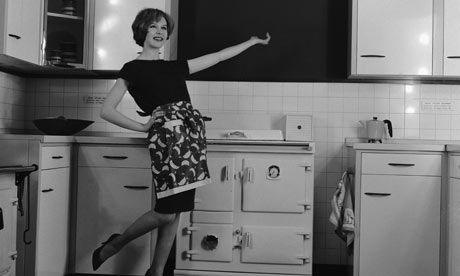 A housewife proudly displays her new fitted kitchen and Rayburn, circa 1960